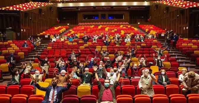 Personas mayores que ya están inmunizadas contra el coronavirus van al teatro en Sevilla para celebrarlo.